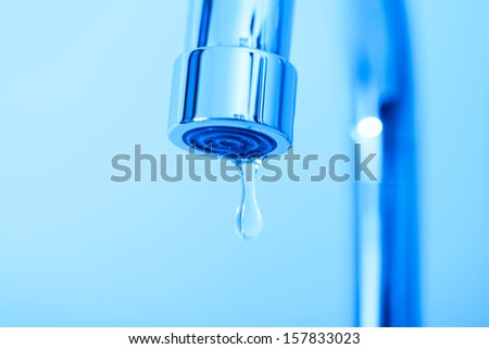 Metal faucet with water drop, in blue tones - stock photo