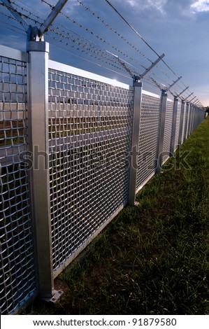 Metal fence Part of a metal grid fence with barbed wire at the top - stock photo