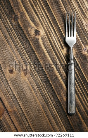 metal fork on a wooden surface, closeup - stock photo