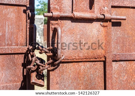 Metal gate closed with chain and padlock - stock photo