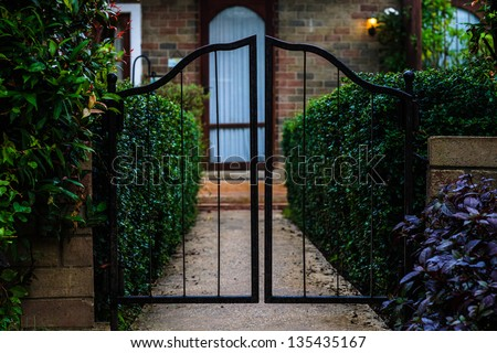 Metal gate in front of the brick house - stock photo