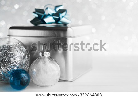 Metal gift box with blue bow and xmas baubles on white glitter background. Merry christmas card. Winter holidays. Xmas theme. Happy New Year. - stock photo