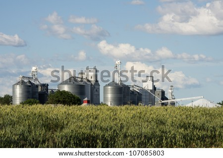 Metal grain silos and elevators under cloudy blue sky - stock photo