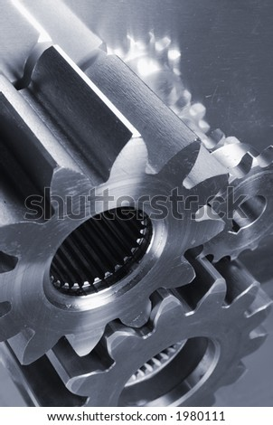 metal-grey gears, cogs connecting against brushed titanium - stock photo
