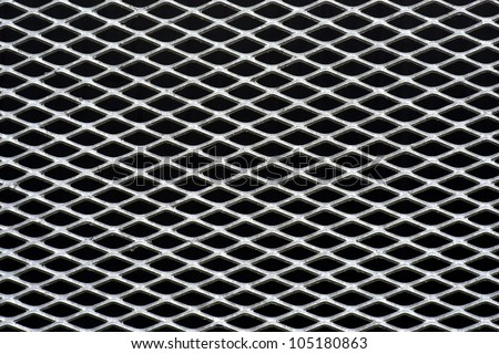 metal grid with regular pattern on black background - stock photo
