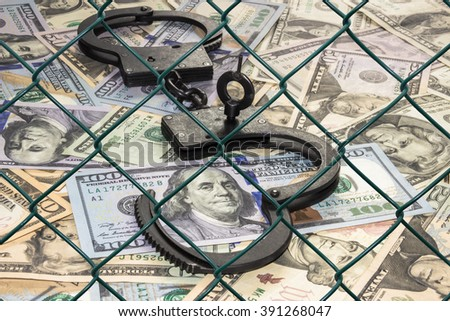 Metal handcuffs with the key on the background of dollars under wire netting (lattice) - stock photo