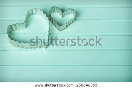Metal heart shaped cookie cutters on a retro turquoise background - stock photo