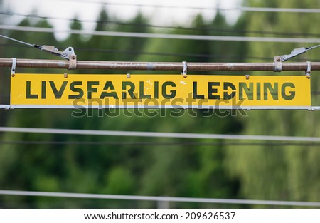 Metal high voltage danger sign and railway electric overhead contact wire all over. In swedish - stock photo