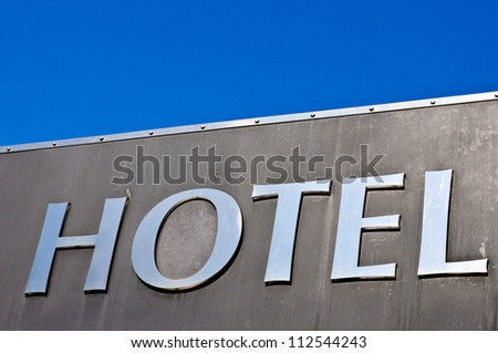 Metal hotel sing on the clear sky - stock photo