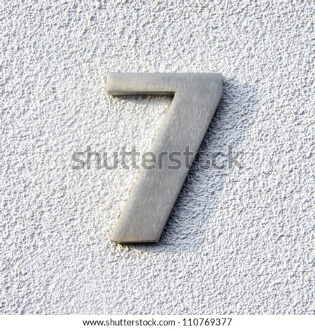 metal house number seven on a plastered white wall. - stock photo