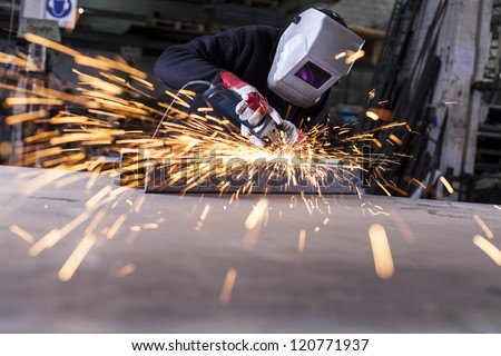 Metal industry worker grinding with mask on the face - stock photo
