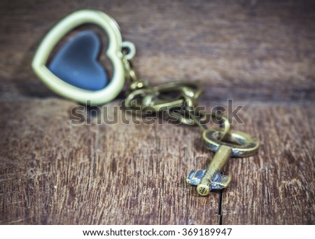 metal key and metal heart key chain on wooden background, concept of success  - stock photo