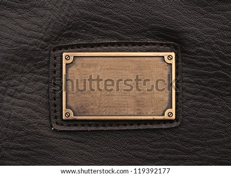 metal label on old black leather background - stock photo