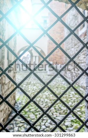 Metal lattice in Wawel. Wawel is fortified architectural complex erected over many centuries atop limestone outcrop on left bank of Vistula river in Krakow, Poland. - stock photo