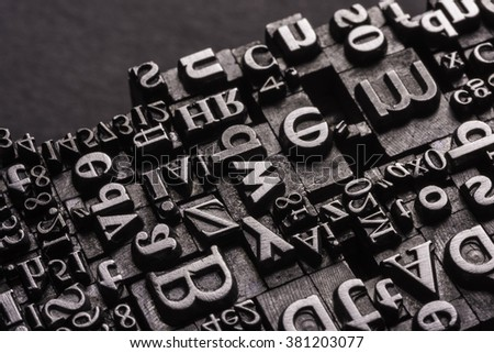 Metal Letterpress Types. A background from many historic typographical letters in black and white with black background.  - stock photo
