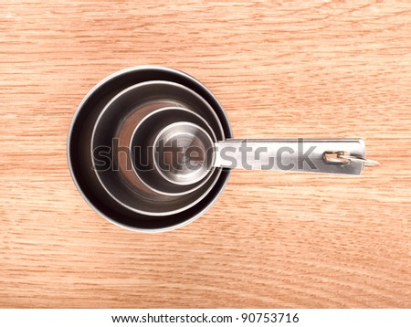 Metal measuring spoons on wood table - stock photo