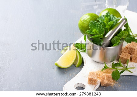 Metal mortar and pestle with fresh mint and ingredients for  mojito, caipirinha cocktails and other drinks. Selective focus. Background with empty copy space. - stock photo