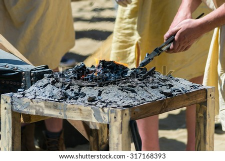 Metal products are heated on the coals in the forge furnace. Fifth International historical festival Times and Epochs 2015 - Ancient Rome - stock photo