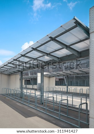 Metal railings of bicycle parking lot with glass canopy - stock photo