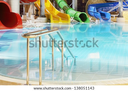 Metal railings, pool and multi-colored water slides in indoor aquapark. - stock photo