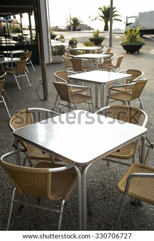 Metal rattan empty tables and chairs outdoor of restaurant. Front view. Have a place for text. - stock photo