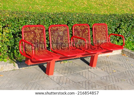 Metal red bench on park - stock photo