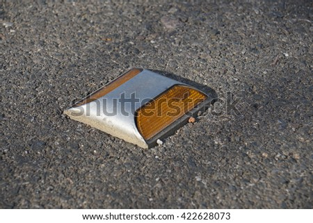 Metal road stud with yellow reflector on asphalt road - stock photo
