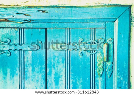 Metal rusty hinges on a pair of blue wooden shutters - stock photo