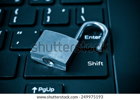 metal security lock left unlock on computer keyboard - security breach concept in computer - stock photo