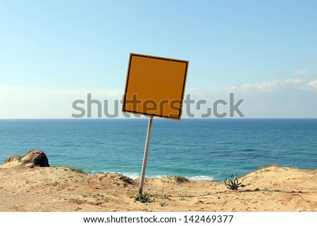 Metal sign on the edge of a cliff on blue sky background with space for your text or design - stock photo