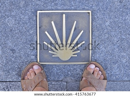 Metal signal in asphalt, Way of St. James in Spain, man's feet in sandals on sidewalk.From above - stock photo