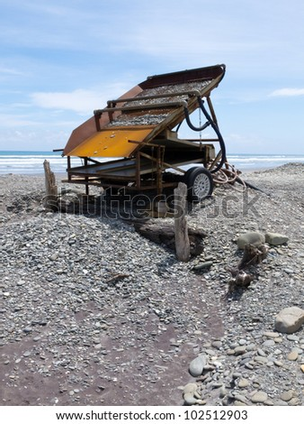 Metal sluice box on placer mining claim for extracting alluvial gold dust from gravel beach of West Coast of New Zealand South Island - stock photo