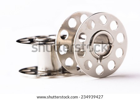 Metal spool of thread isolated on white - stock photo