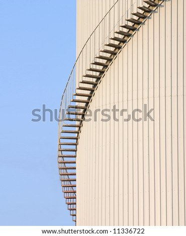 Metal staircase swirling around a storage tank set against blue sky - stock photo
