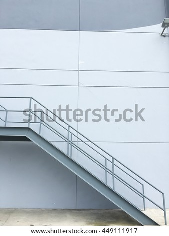 Metal stairs on concrete wall - stock photo