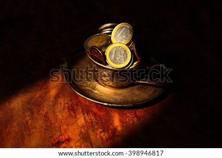 Metal, steel cup and saucer with money euro cent on a dark background old. sunlight - stock photo