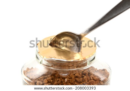 Metal teaspoon breaking the foil seal on a jar of instant coffee granules for the first time, isolated on a white background - stock photo