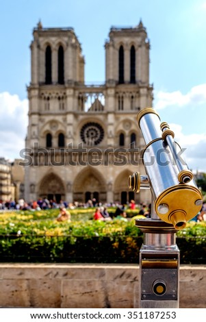 Metal Telescope in front of Notre Dame Cathedral in Paris, France - stock photo