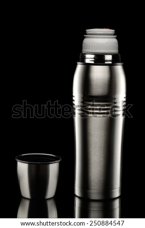 Metal thermos on black background - stock photo