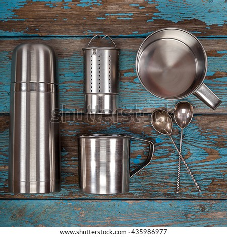 Metal thermos, strainer, mugs and spoons on a wooden background. Kitchenware. Tea accessories. - stock photo