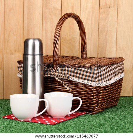 metal thermos with cups and basket on grass on wooden background - stock photo