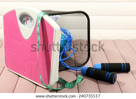 Metal trash bin with sport equipment, crumpled paper and weight scale on wooden floor and white wall background - stock photo