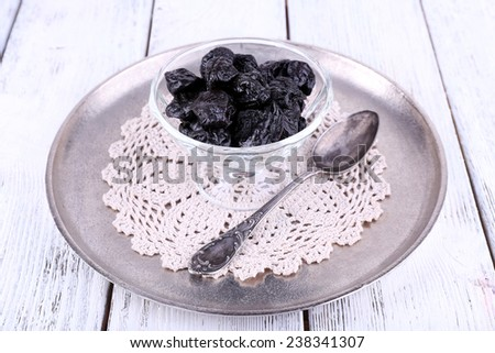 Metal tray with glass bowl of prunes, lace doily and spoon on color wooden background - stock photo