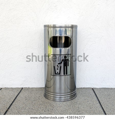 metal waste bin against a wall - stock photo