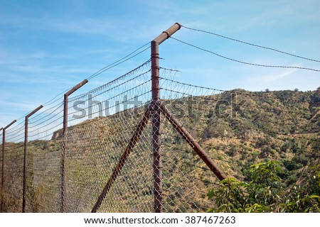 Metal wire fence is run down and broken along top of a hill. - stock photo