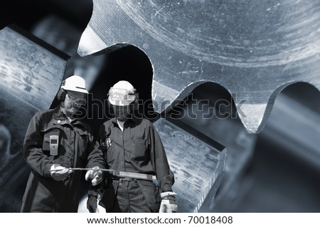 metal-works. engineers and large gear machinery in background, metallic blue toning - stock photo