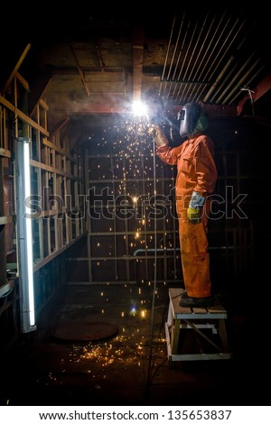 Metal wroker in a factory grinding with sparks - stock photo