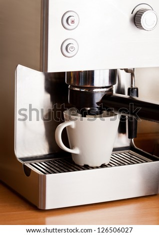 Metall coffee machine and cup of fresh coffee with foam - stock photo