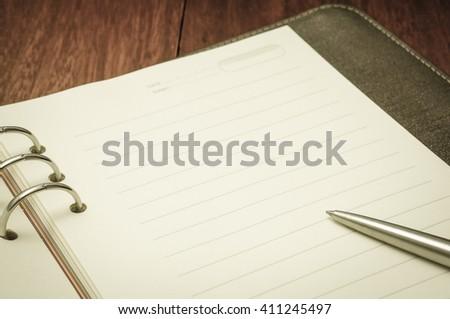 Metallic ball pen on notebook in vintage style.Selective focus. - stock photo