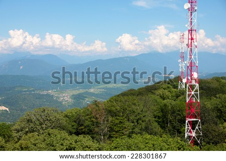 metallic broadcasting tower on the top of high mountain - stock photo